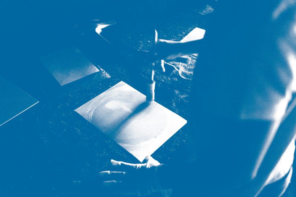 Papier mit der Fotochemie bestreichen beim Cyanotypie-Workshop der Offenen Jugendarbeit Bregenzerwald.